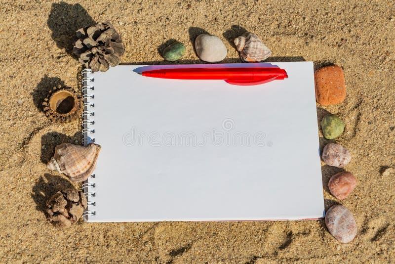 Een witte blocnote met de witte lente met een rode ballpointpen ligt op een gele zandoppervlakte en heeft een de zomerreis stock afbeelding