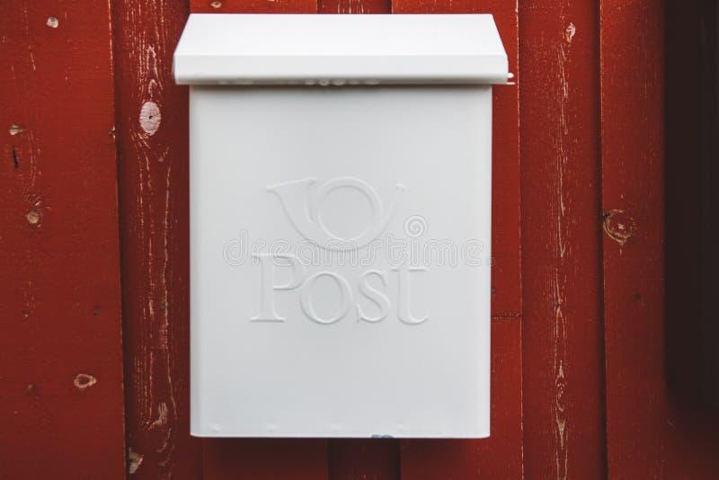 Een witte brievenbus op een rode houten muur met een rode deur stock foto