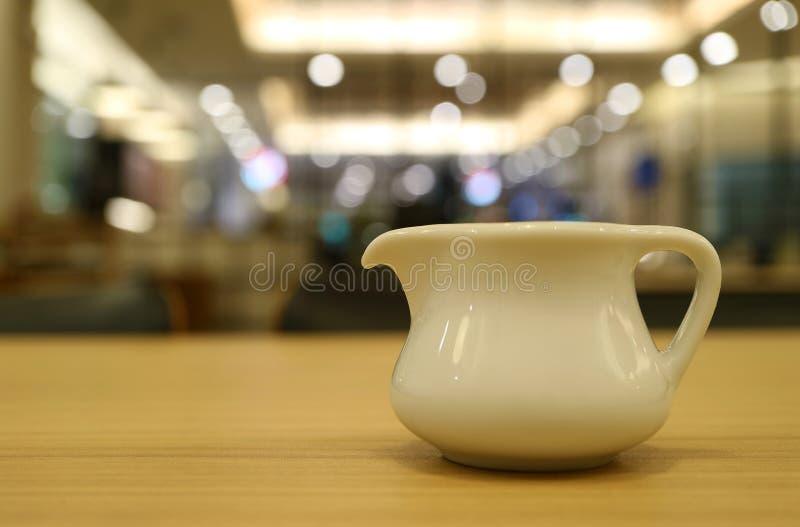 Een witte ceramische waterkruik op koffie` s houten lijst met bokeh binnenlandse verlichting op de achtergrond stock fotografie