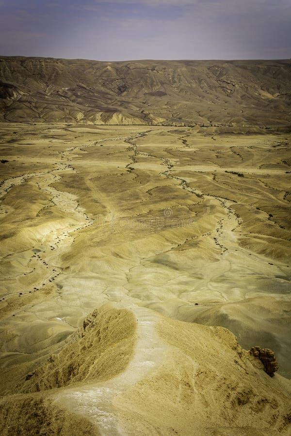 Een witte dalende weg door een woestijnklip stock fotografie