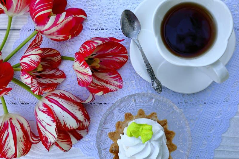 Een witte kop thee met een schotel en een lepel, een dessert van gebakje, een boeket van rood-en-witte tulpen stock afbeelding