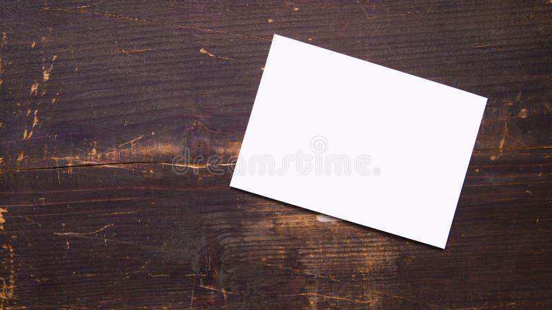 Een witte lege prentbriefkaar op een houten achtergrond stock fotografie