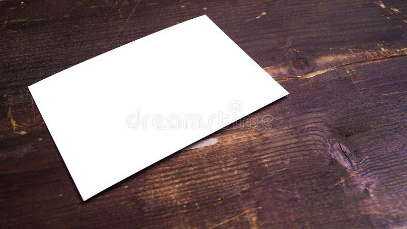 Een witte lege prentbriefkaar op een houten achtergrond stock afbeelding