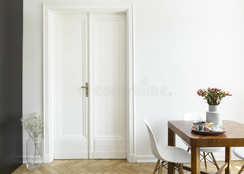 Een witte muur met dubbele deur naast een houten ontbijtlijst en stoelen in een eetkamerbinnenland Echte foto stock foto's