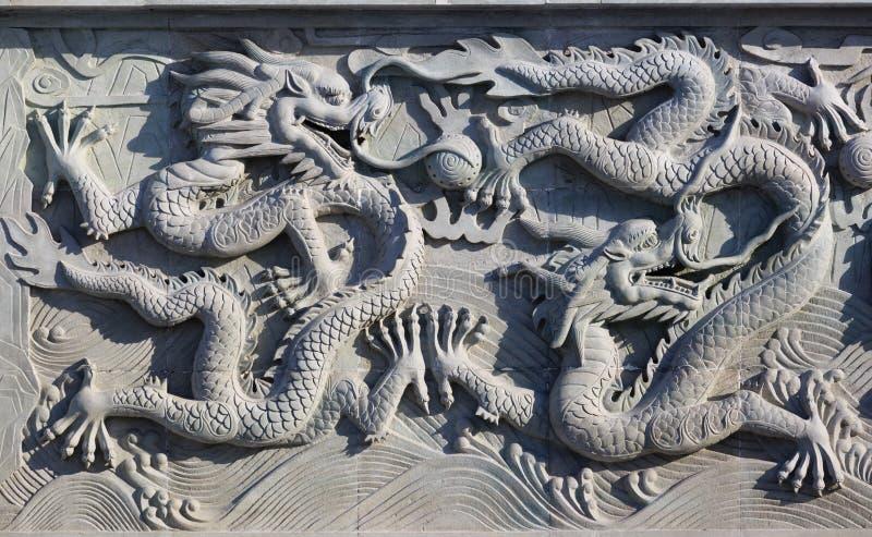 Een witte muur met het beeldhouwwerkachtergrond van de draaksteen stock foto
