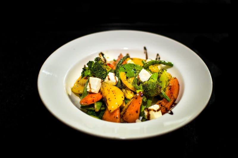 Een witte plaatopstelling die een heerlijk huis tonen maakte salade bestaand uit een verscheidenheid van groenten stock foto