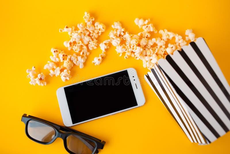 Een witte smartphone, 3d glazen, een zwart-wit gestreept document vakje en een verspreide popcorn liggen op een gele achtergrond stock foto's
