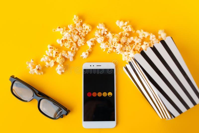 Een witte smartphone met smilies op het scherm, 3d glazen, een zwart-wit gestreept document vakje en een verspreide popcorn stock foto