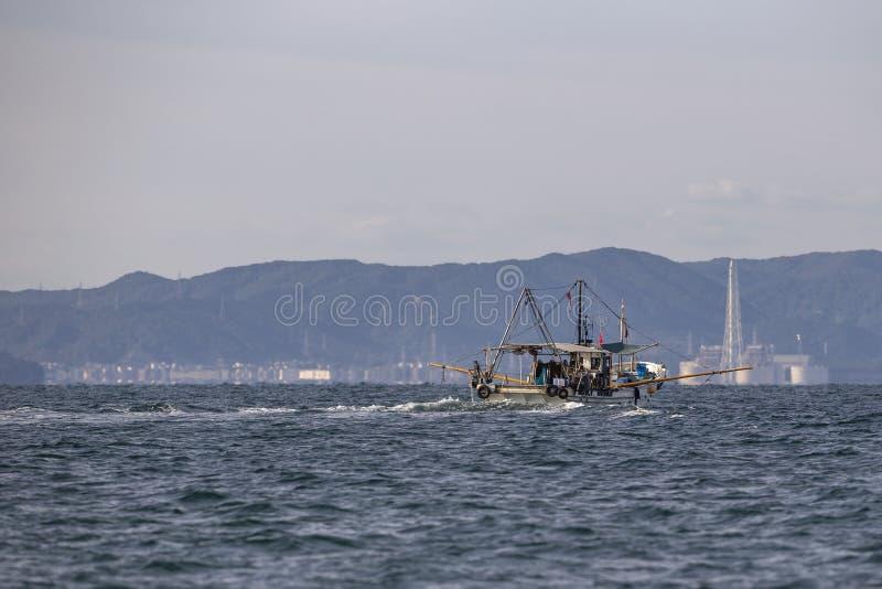 Een witte vissersboot die bij de baai van Osaka met stad lopen bakground royalty-vrije stock foto's