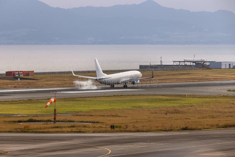 Een witte vliegtuig het landen aanraking neer bij de luchthaven van Osaka, Japan royalty-vrije stock foto's