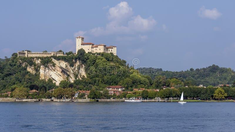 Een witte zeilboot vaart op het Maggiore-meer bij de Rocca di Angera, Varese, Italië stock afbeelding