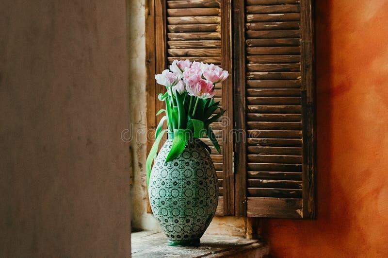 Een zacht geconcentreerd boeket van bloemen in een vaas op een venstervensterbank royalty-vrije stock foto's