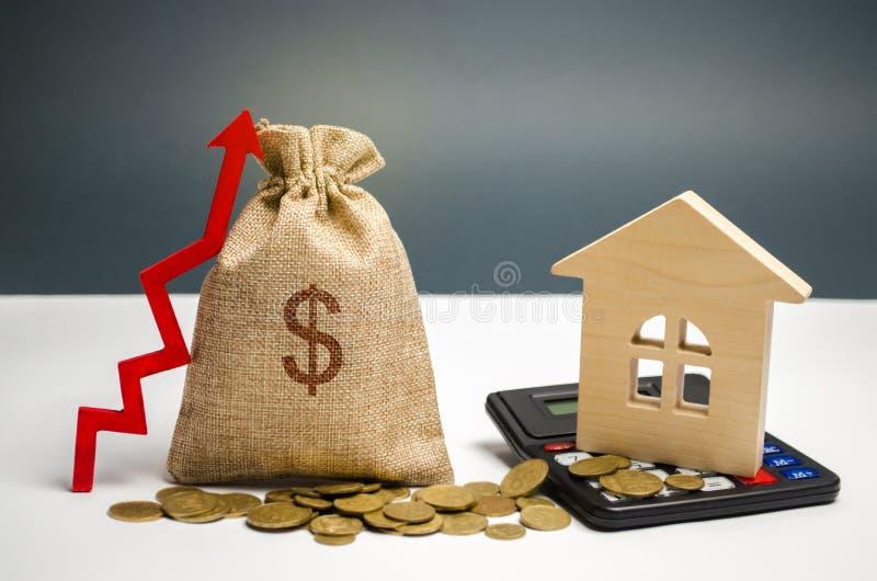 Een zak met een dollarteken, een omhooggaande pijl en een huis Het concept het verhogen van de waarde van onroerende goederen De  royalty-vrije stock foto