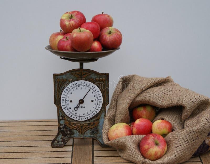 Een zak met rode appelen voor het wegen op de oude keukenschaal die wordt gevuld stock afbeelding