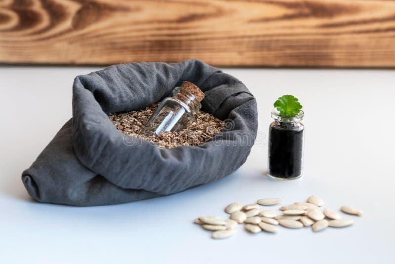 In een zak natuurlijk die vlas met zaden van installaties wordt gevuld is een glaskruik voor het opslaan van zaden Naast de zak i royalty-vrije stock foto