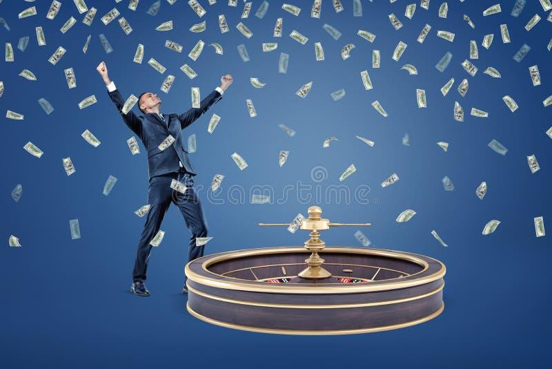 Een zakenman bevindt zich dichtbij een casinoroulette en onder regen van geldrekeningen stock fotografie