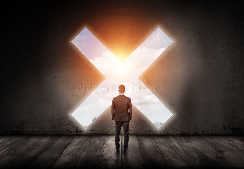 Een zakenman bevindt zich met zijn gedraaide achter en onderzoekt een kruisvormig gat in een concrete muur stock fotografie