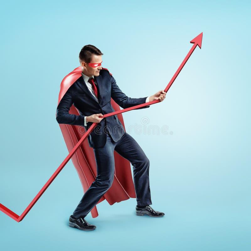 Een zakenman die een rode superherokaap dragen die een rode statistiekpijl met kracht op blauwe achtergrond proberen te houden stock foto's