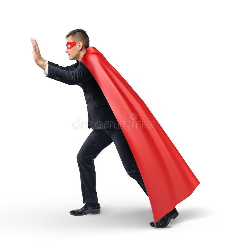 Een zakenman in een superhero rode kaap en een oog maskeren het duwen op een onzichtbaar voorwerp in zijaanzicht royalty-vrije stock foto