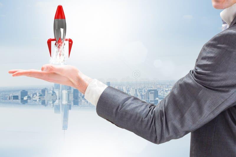 Een zakenman houdt een raket opstijgend van zijn hand tegen blauwe achtergrond royalty-vrije stock afbeeldingen