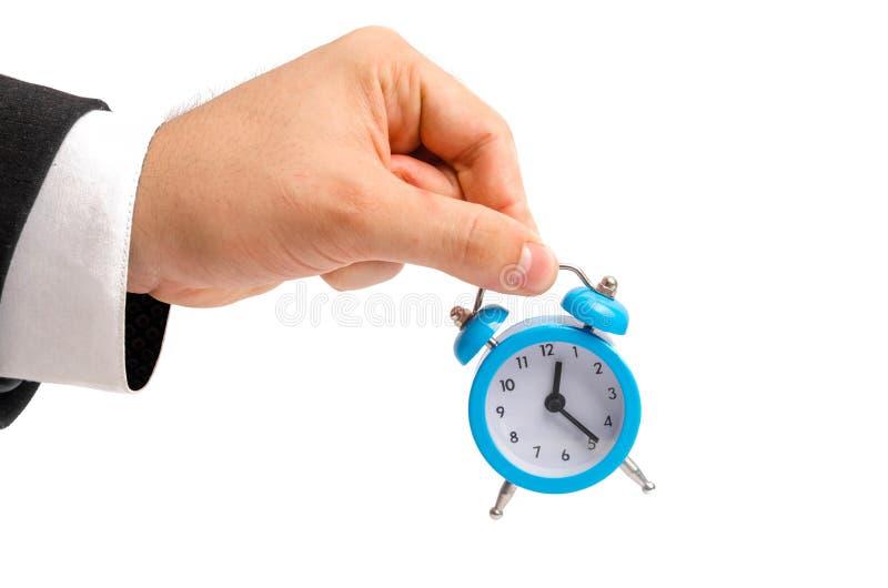 Een zakenman houdt een wekker Horloge ter beschikking Het concept loon per uur, tijd Laat voor het werk Volledig of onvolledig ta stock fotografie