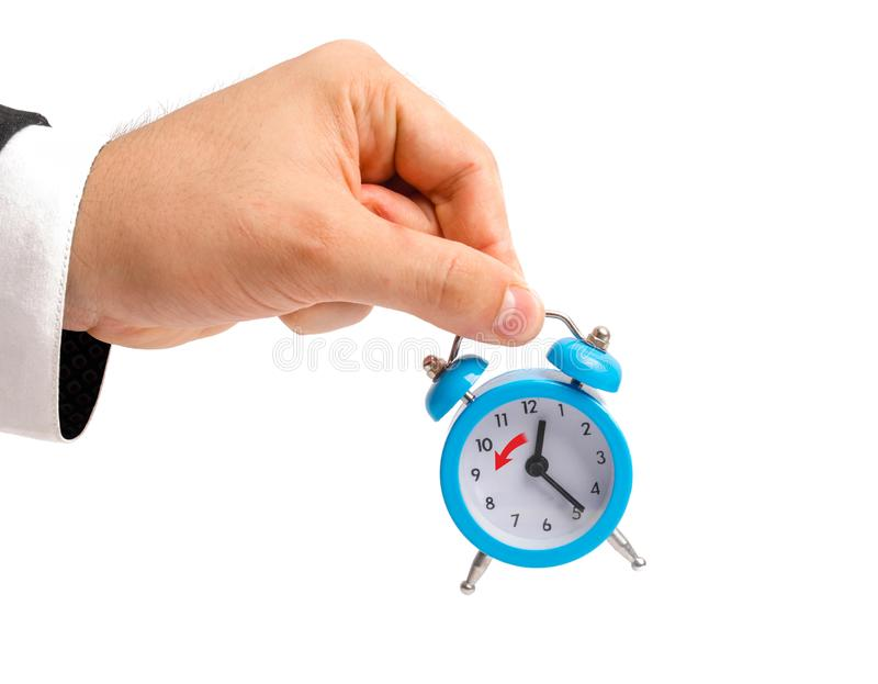 Een zakenman houdt een wekker Overgang naar de wintertijd, overdracht van uren aan een uurrug Horloge ter beschikking Het concept stock afbeeldingen