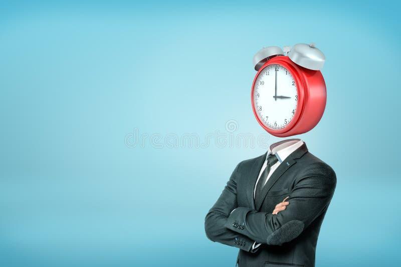 Een zakenman met gekruiste wapens bevindt zich in helft-draai met een grote rode wekker in plaats van zijn hoofd stock foto's