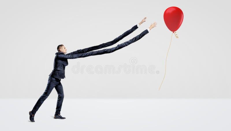 Een zakenman met uiterst lange wapens die een rode ballon met een gift gouden lint proberen te vangen royalty-vrije stock foto