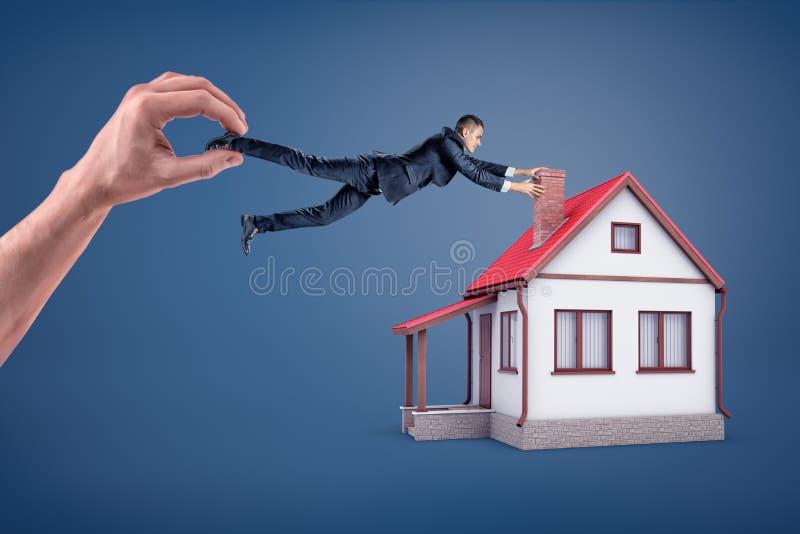 Een zakenman probeert om op een schoorsteen van een plattelandshuisje te houden terwijl hij weg door een reuzehand wordt gesleept stock foto's