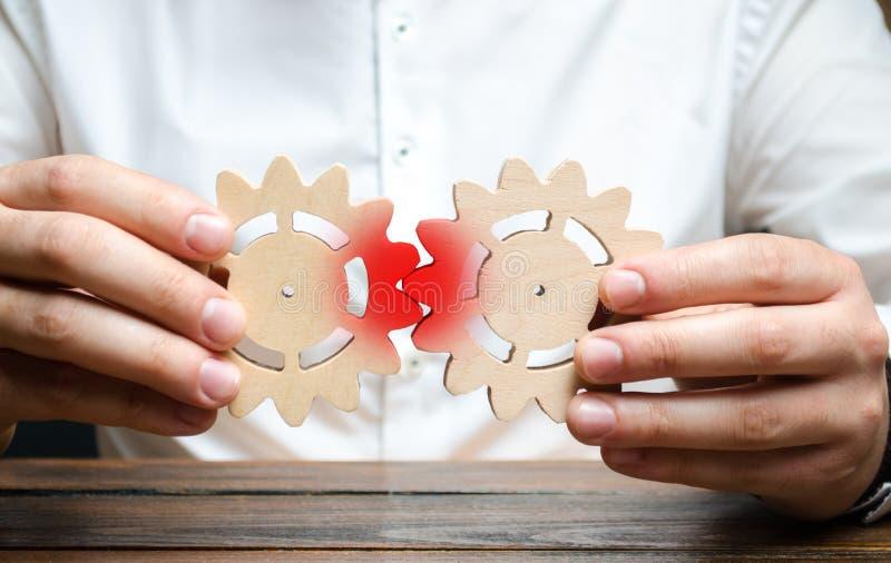 Een zakenman probeert om twee toestellen samen te brengen en slaagt er niet in om tot hen het werk te maken Het concept de onmoge stock foto's