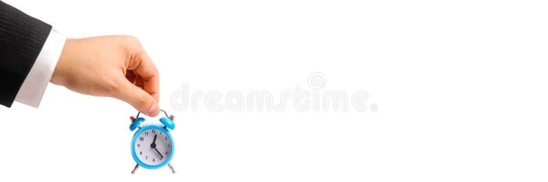 Een zakenman` s hand houdt een blauwe wekker op een witte achtergrond concept de stroom van tijd, tijd aan actie Per uur betaal v royalty-vrije stock afbeelding