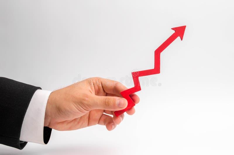 Een zakenman` s hand houdt een rode pijl op een witte achtergrond tegen Het concept het opheffen van en het vermenigvuldigen van  royalty-vrije stock afbeelding