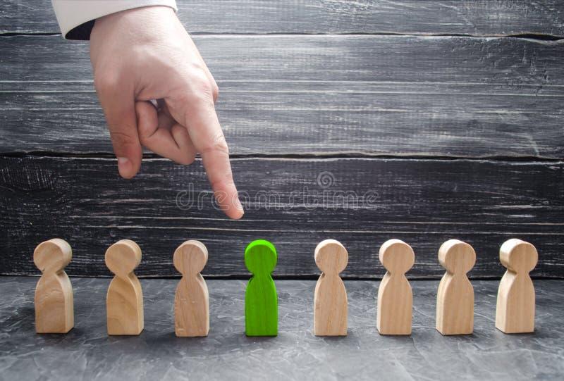 Een zakenman` s hand richt aan een groen houten menselijk cijfer Het concept het onderzoek naar arbeiders, beheer van personeel stock foto