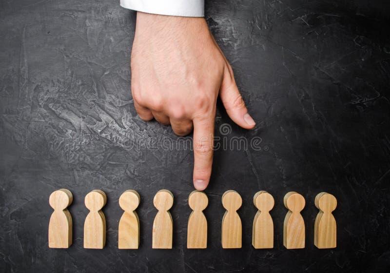 Een zakenman` s hand richt aan een houten menselijk cijfer Het concept het onderzoek naar arbeiders, beheer van personeel stock afbeeldingen