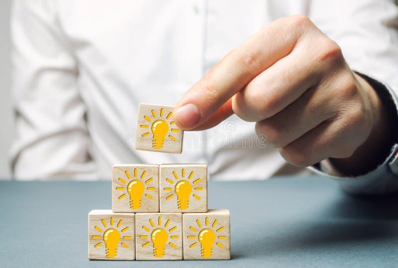 Een zakenman zet houten blokken met een gloeilamp van een idee of een inspiratie Generatie van innovatieve bedrijfsideeën creatie royalty-vrije stock afbeeldingen