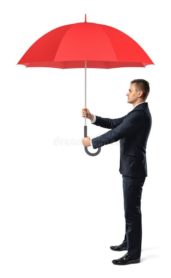 Een zakenman in zijaanzicht houdt een open rode paraplu in allebei voorzijde van hem indient royalty-vrije stock fotografie