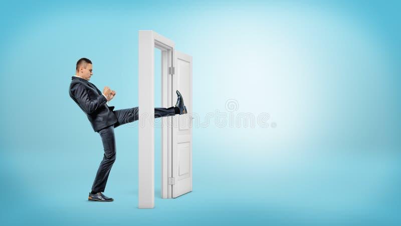 Een zakenman in zijaanzicht schopt een kleine witte deur open met zijn been op blauwe achtergronden royalty-vrije stock fotografie