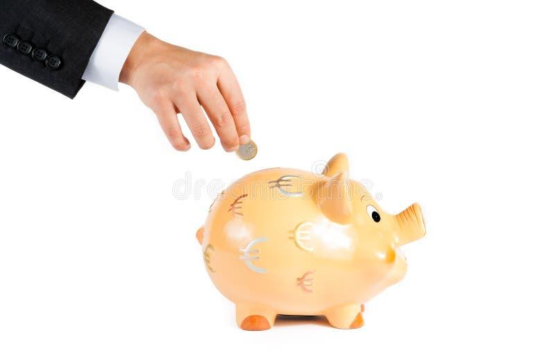 Een zakenmanhand die een muntstuk in een geïsoleerd spaarvarken, concept voor zaken opnemen en bespaart geld royalty-vrije stock foto