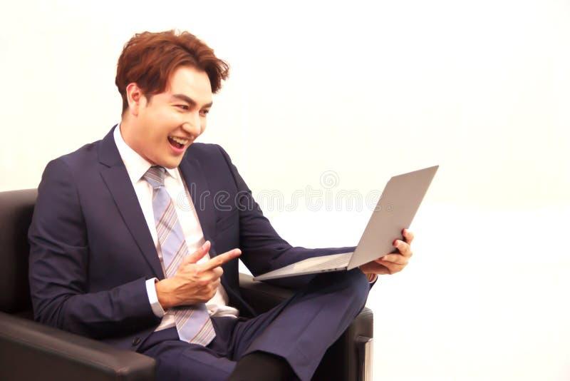 Een Zakenmanzitting op de zwarte bank, stelt gelukkig, richtend zijn vinger op de monitor van laptop computer na het controleren stock foto's