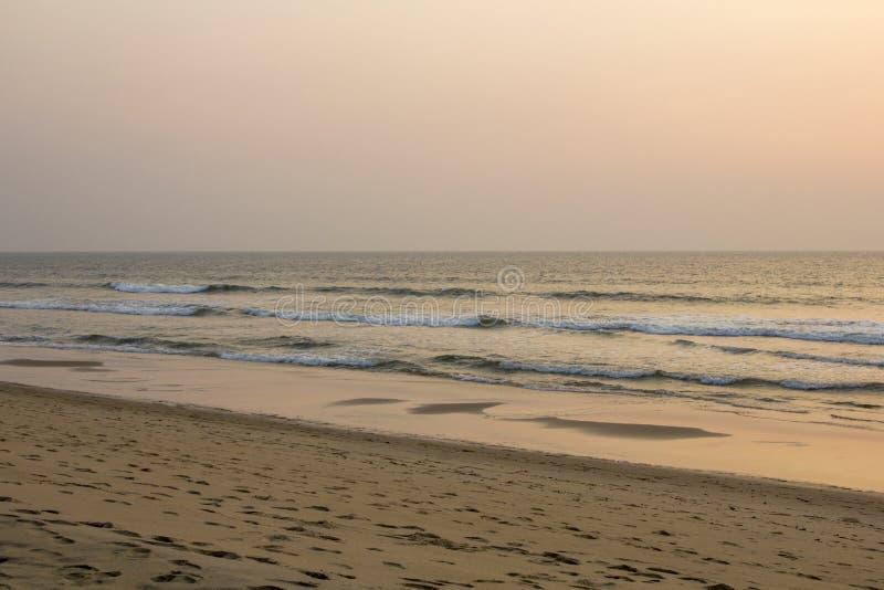 Een zandig strand met voetafdrukken op de achtergrond van het overzees onder een grijze roze blauwe hemel van de avondzonsonderga stock foto