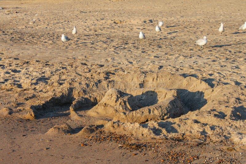 Een zandkasteel dat gedeeltelijk door golven op een verlaten strand met strandlopers vernietigd is die rond lopen royalty-vrije stock afbeeldingen