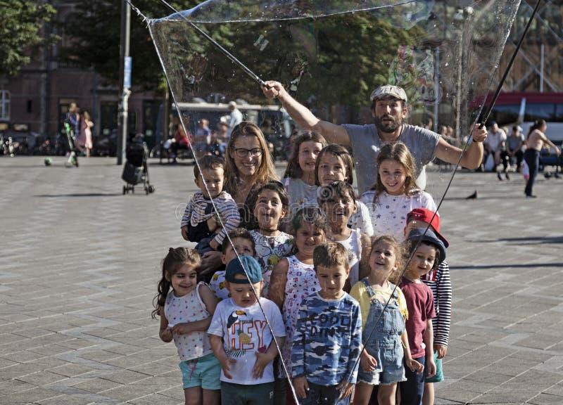 Een zeepbelkunstenaar laat kinderen door een grote bel worden gevangen royalty-vrije stock afbeeldingen