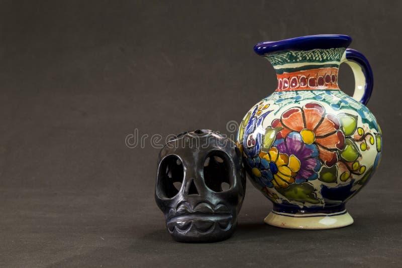 Een zeer ernstige Talavera Puebla vaas met een zwarte Oaxaca-schedel stock foto's