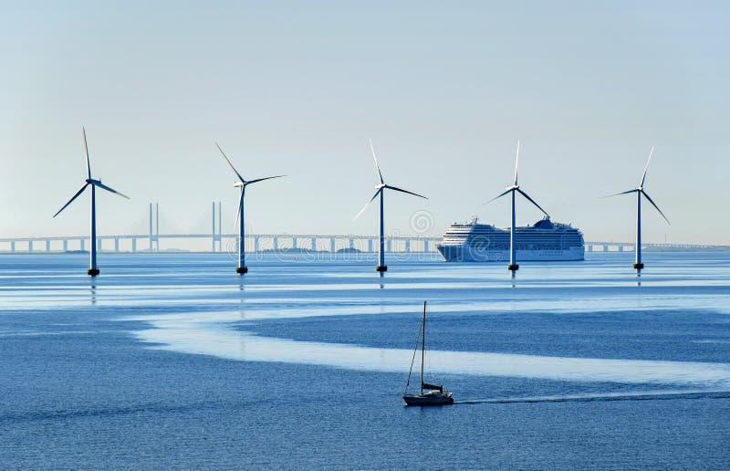 Een zeer groot passagiersschip en een kleine zeilboot gaan zeewindturbines dichtbij de Oresund-Brug over tussen Denemarken en Zwe royalty-vrije stock foto