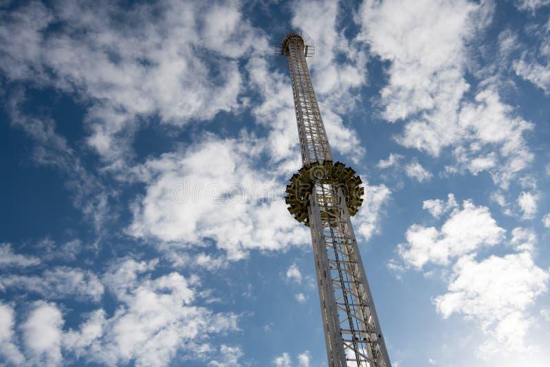 Een zeer lange vrije daling funfair berijdt met een blauwe hemel en een witte griep royalty-vrije stock afbeelding
