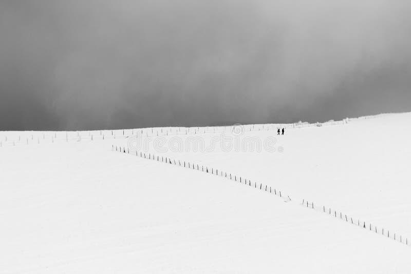 Een zeer minimalistic mening van twee verre die mensen over een berg door sneeuw, dichtbij een omheining wordt behandeld royalty-vrije stock foto's