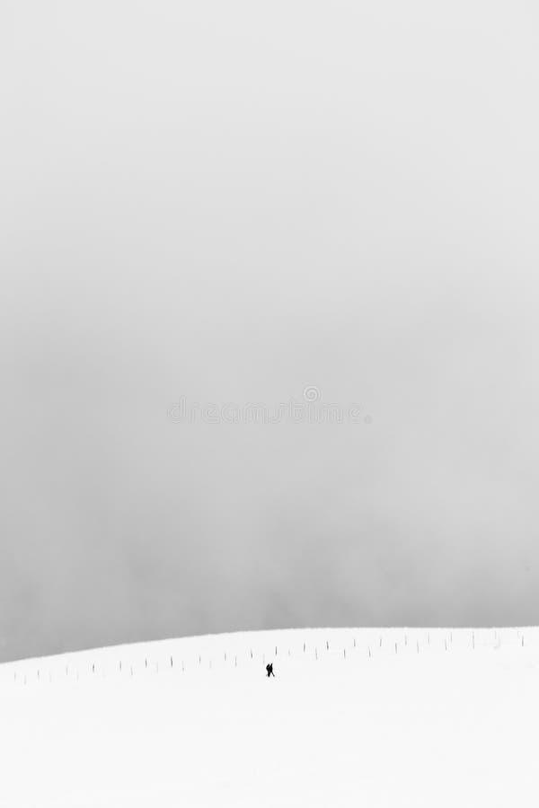 Een zeer minimalistic mening van twee verre die mensen over een berg door sneeuw, dichtbij een omheining wordt behandeld royalty-vrije stock afbeelding
