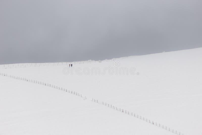 Een zeer minimalistic mening van twee verre die mensen over een berg door sneeuw, dichtbij een omheining wordt behandeld stock foto