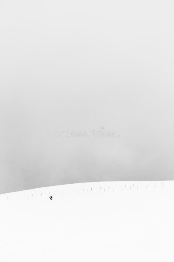 Een zeer minimalistic mening van twee verre die mensen over een berg door sneeuw, dichtbij een omheining wordt behandeld stock fotografie