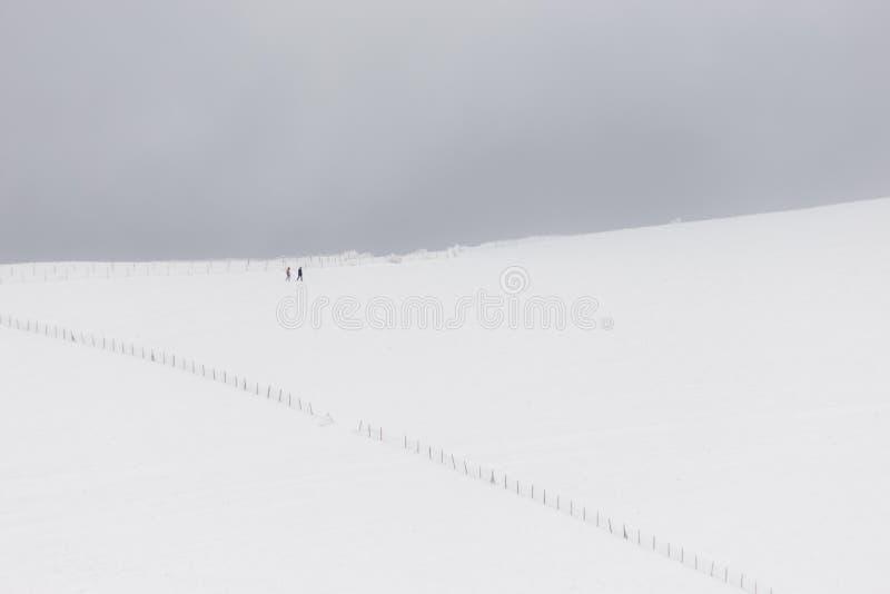 Een zeer minimalistic mening van twee verre die mensen over een berg door sneeuw, dichtbij een omheining wordt behandeld stock foto's